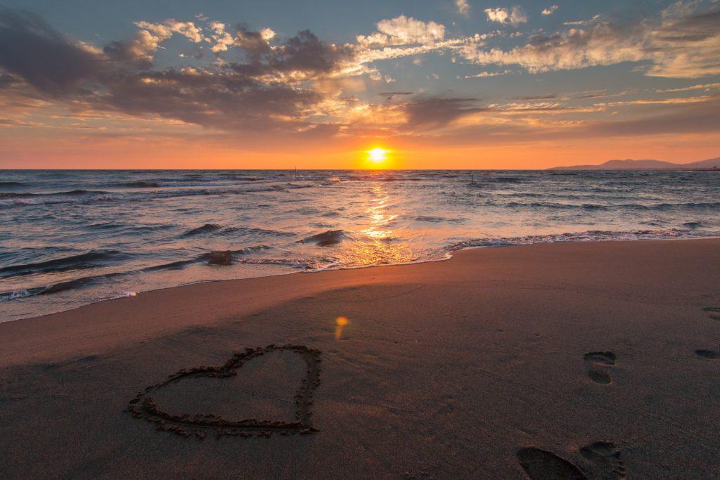 Atardecer con un corazón dibujado en la playa
