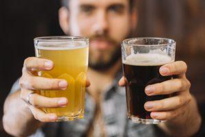 Hombre mostrando dos tipos de cervezas